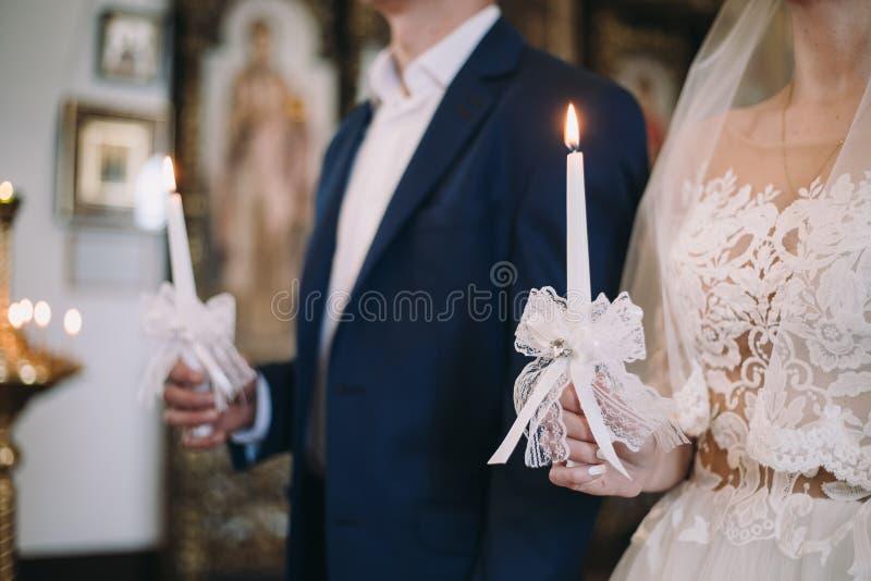 O par novo em uma cerimônia de casamento está guardando umas velas ardentes em suas mãos fotografia de stock royalty free