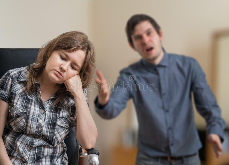 O par novo está discutindo O homem é gritaria e explicação de algo à mulher triste fotografia de stock royalty free
