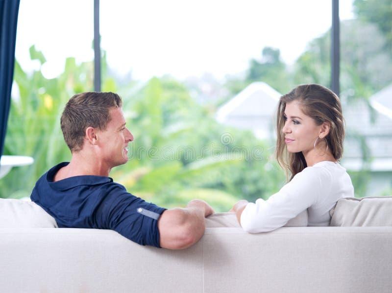 O par novo est? sentando-se no sof? na casa de ver foto de stock royalty free