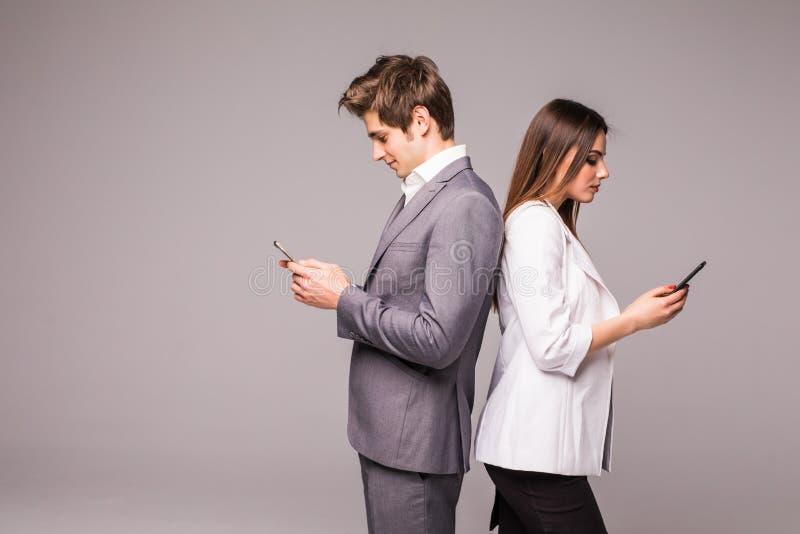O par novo está usando telefones espertos e está sorrindo ao estar de volta à parte traseira em um fundo cinzento imagem de stock