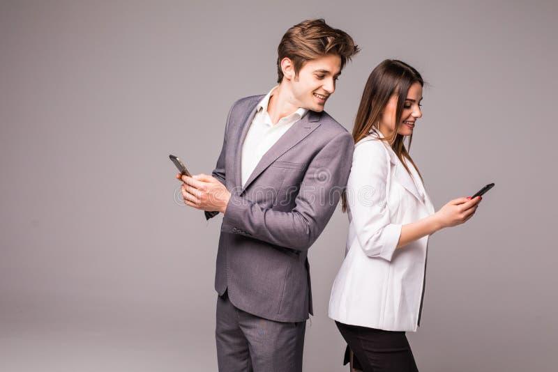 O par novo está usando telefones espertos e está sorrindo ao estar de volta à parte traseira em um fundo cinzento Olhar do homem  fotos de stock royalty free