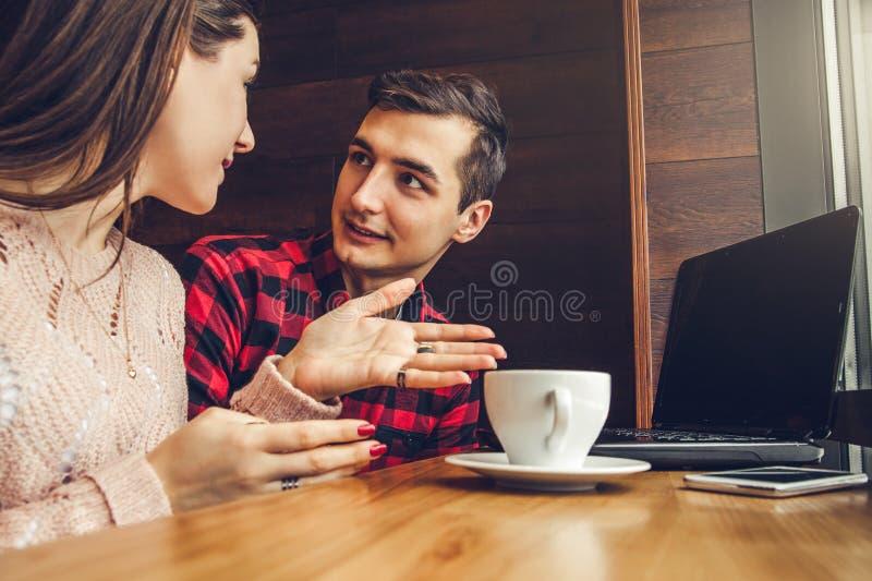 O par novo fala e aprecia o café no café usando um portátil fotografia de stock