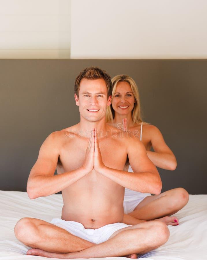 O par novo que faz a ioga move-se na cama imagens de stock
