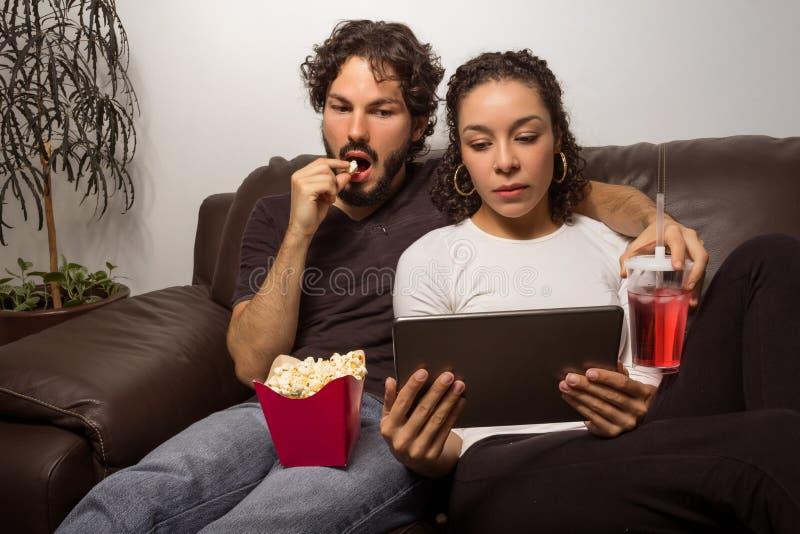 O par olha o filme na tabuleta Eles que sentam-se assim no sofá em h imagens de stock