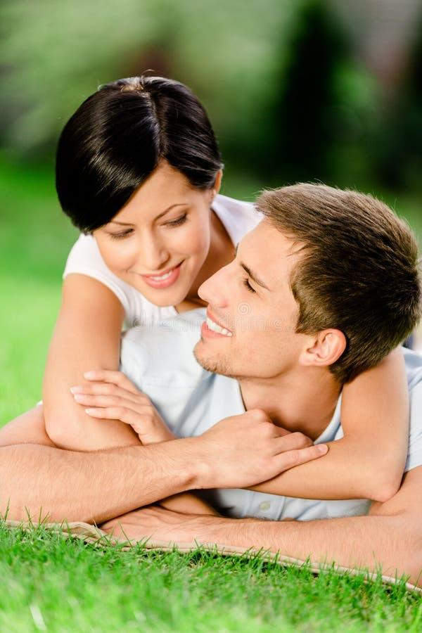 O par que encontra-se na grama verde abraça-se fotografia de stock