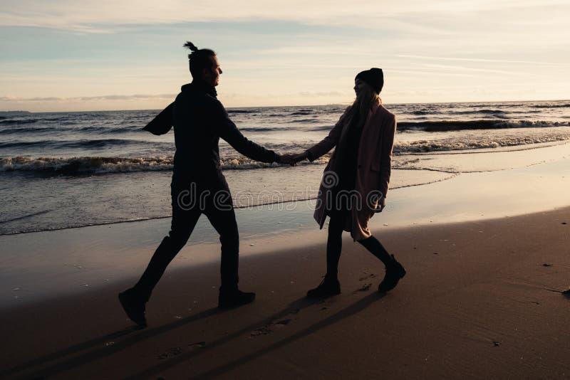 O par romântico feliz que anda na praia perto do oceano, relaxar, guardando entrega-se foto de stock royalty free