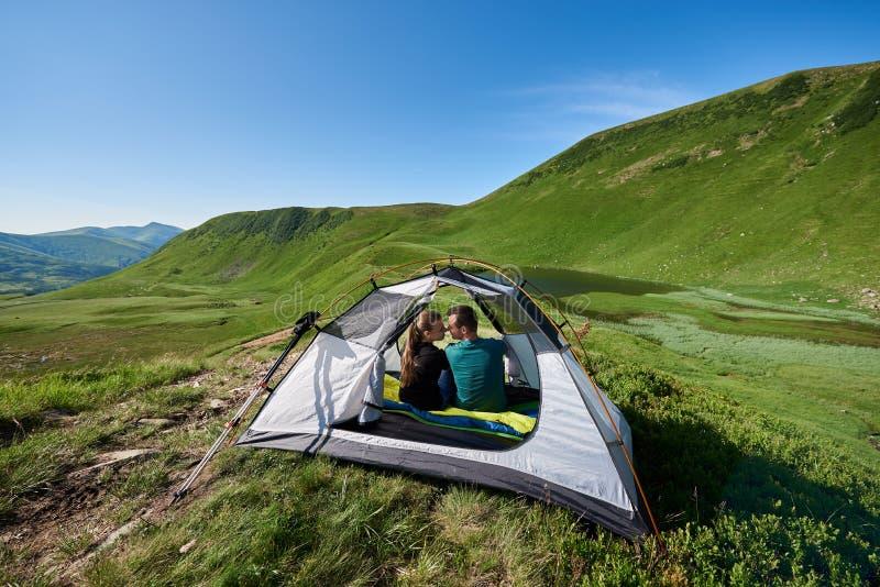 O par romântico senta-se no lago de negligência da montanha da barraca entre montanhas do cenário fotos de stock royalty free