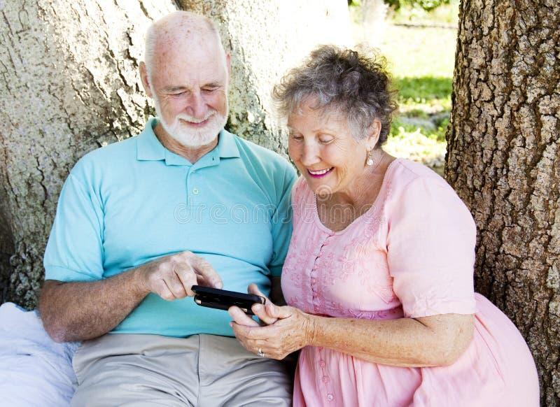 O par sênior lê a mensagem de texto imagem de stock royalty free