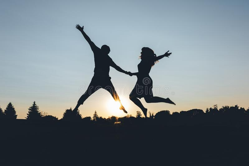 O par salta guardando as mãos no por do sol, quadro da silhueta fotografia de stock royalty free