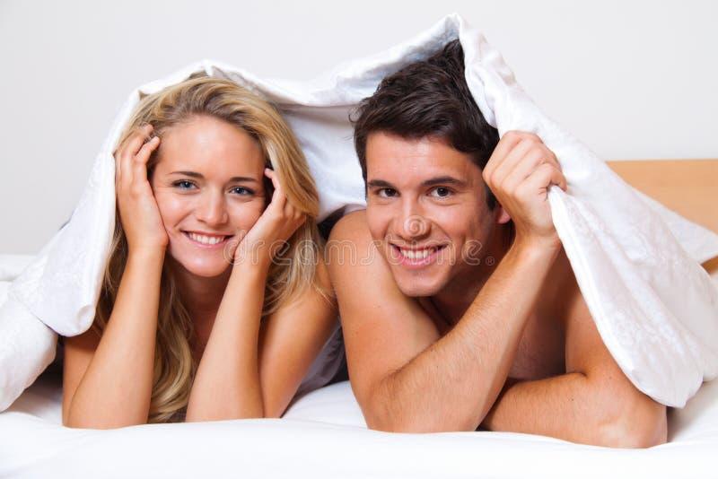 O par tem o divertimento na cama. Riso, alegria e eroticism fotos de stock