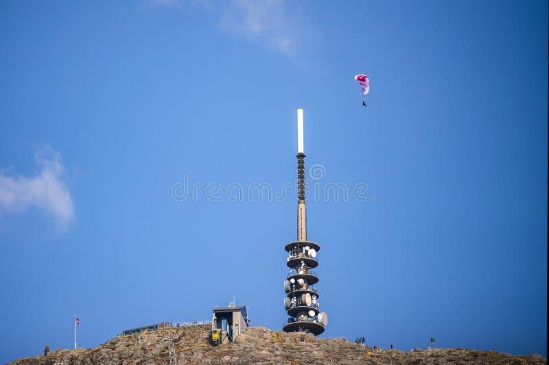 O parag-lider vermelho e branco contra um céu azul sobe sobre uma torre de antena e uma gôndola imagens de stock