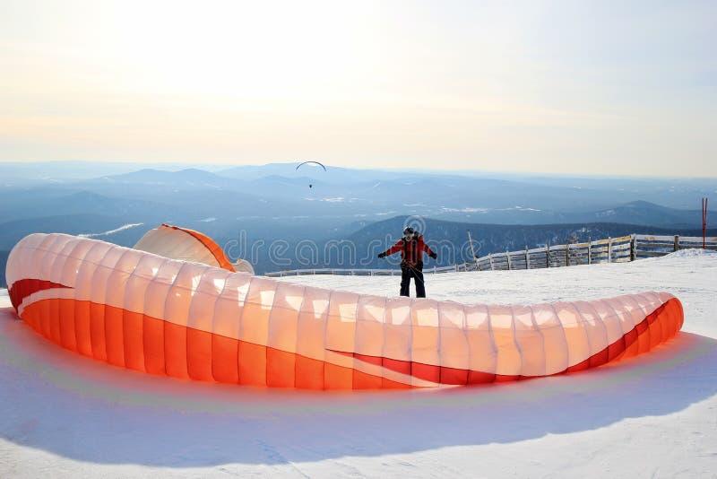 O Paraglider está preparando-se para a decolagem próximo às montanhas Paisagem do inverno fotografia de stock