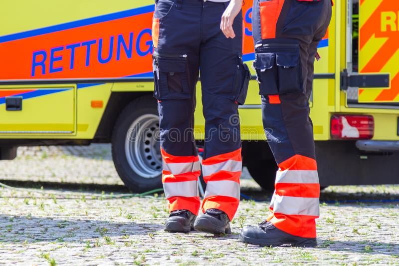 O paramédico fêmea alemão está na frente de um carro da ambulância fotos de stock