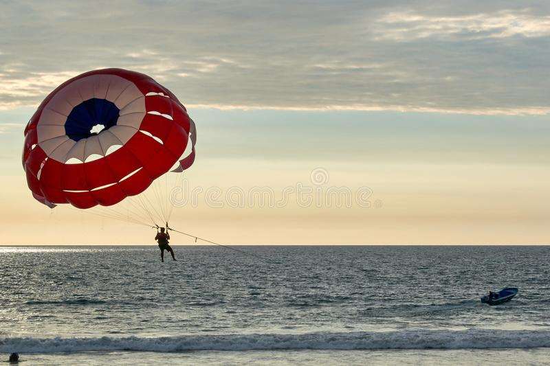 O paraquedas empurrou pela lancha no mar com férias do por do sol foto de stock