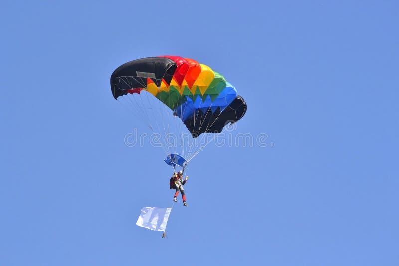 O paraquedista com um paraquedas multi-colorido voa no céu imagem de stock royalty free