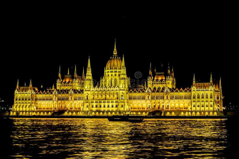 O parlamento de Budapest na instalação da luz do ouro da noite foto de stock royalty free