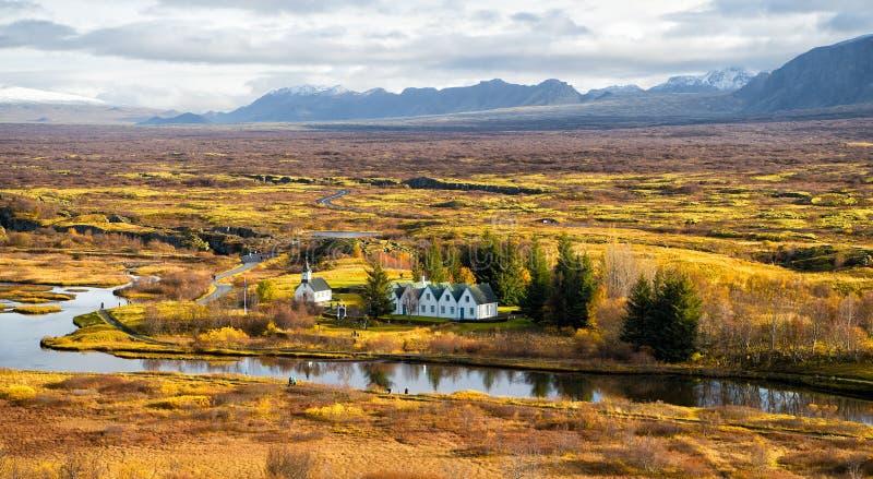 O parque nacional do thingvellir liso em reykjavik entra ao círculo dourado de Islândia campo com rio, igreja, casas fotografia de stock