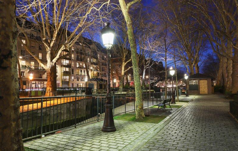 O parque perto do canal St Martin na noite ? canal longo em Paris, conectando o canal de l ?Ourcq ao rio Seine foto de stock royalty free
