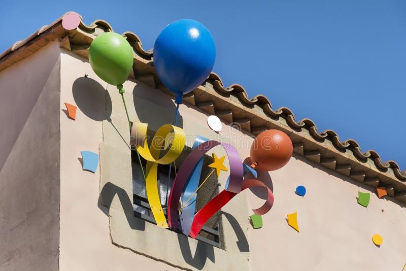 O partido colorido balloons a decoração nas janelas de uma construção fotos de stock