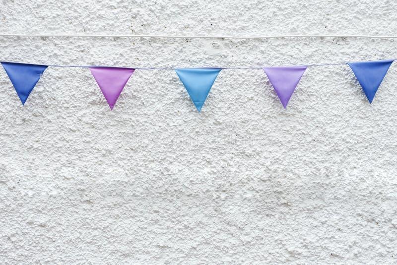 O partido colorido embandeira a estamenha que pendura no fundo branco da parede Projeto mínimo do estilo do moderno fotografia de stock