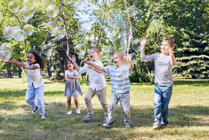 O partido das crianças no parque público verde imagem de stock