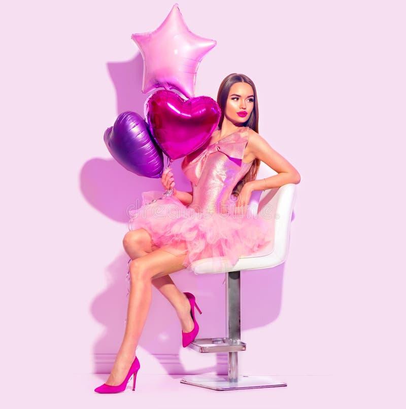 O party girl do modelo de forma da beleza com coração deu forma ao levantamento dos balões de ar, sentando-se na cadeira Festa de imagens de stock