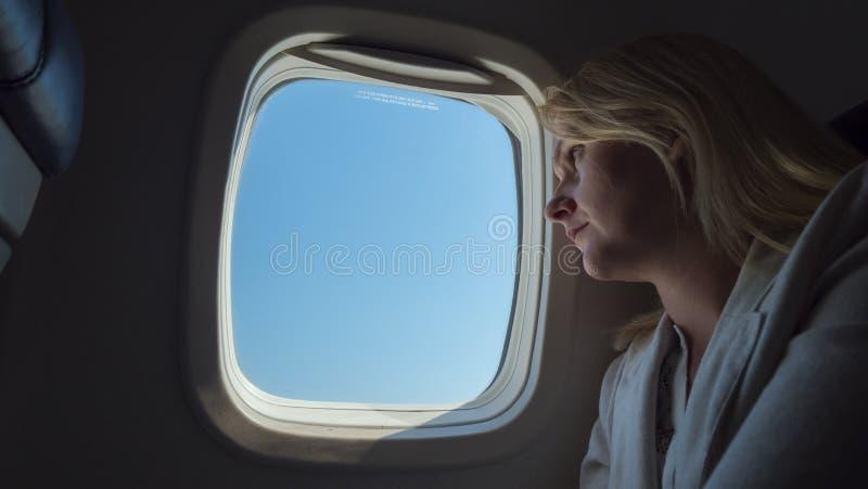O passageiro olha para fora a janela, viajando em um avião fotografia de stock