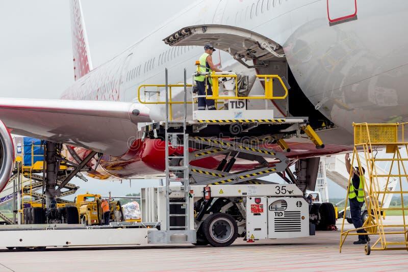 O passageiro que o avião Boeing 777-300 de linhas aéreas de Rossiya apenas aterrou, carga é descarregado dos aviões fotos de stock