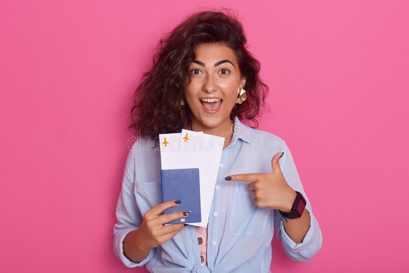 O passaporte bonito alegre da terra arrendada da mulher e os bilhetes planos à disposição, pontos com seu dedo indicador para seu fotos de stock royalty free