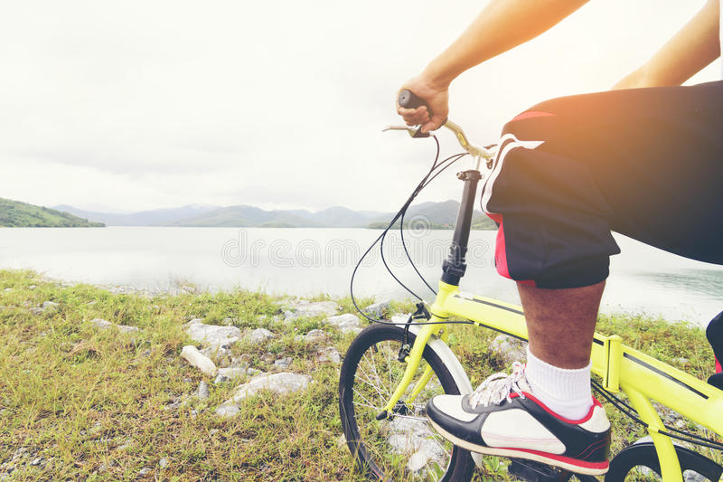 O passeio asiático do homem uma bicicleta e um lago vê fotos de stock