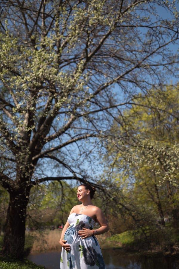 O passeio, o corredor novos da mulher gravida do viajante, girando ao redor e apreciam seu tempo livre do lazer em um parque com imagens de stock royalty free
