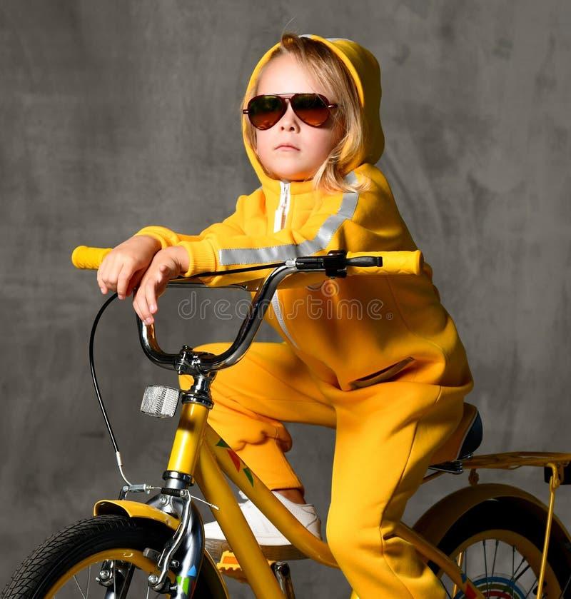 O passeio da criança da moça senta-se na bicicleta amarela nos óculos de sol que olham acima no muro de cimento cinzento fotografia de stock