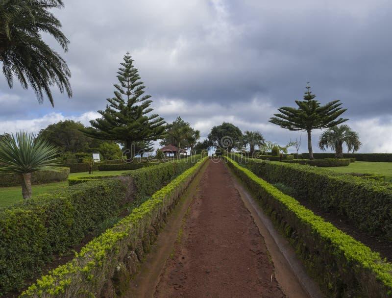 O passeio da sujeira nos jardins no ponto de vista Ponta faz Sossego com arbusto verde, palmeiras e o miradouro altan, Sao Miguel foto de stock