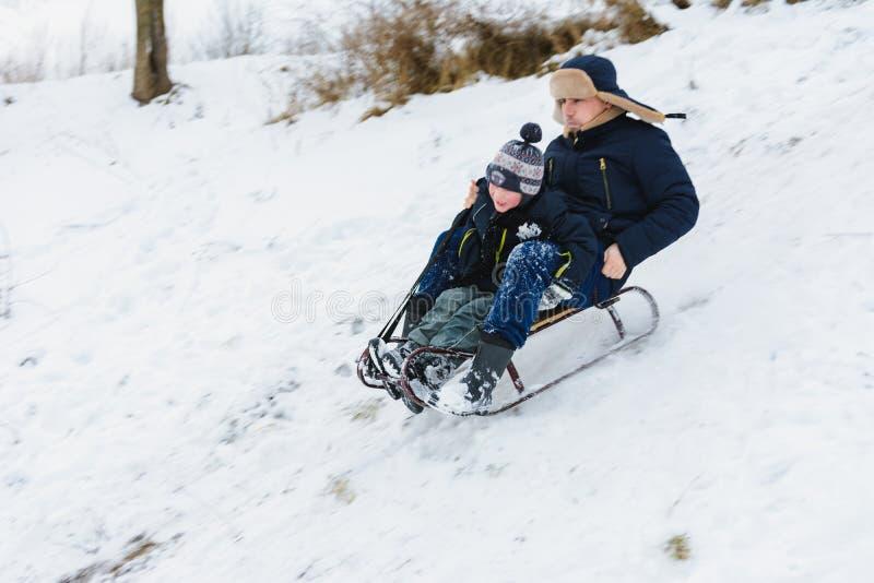 O passeio do paizinho e do filho em sledding, bebê é divertimento foto de stock