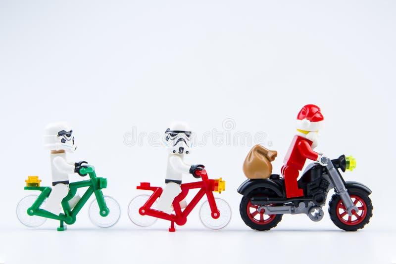 O passeio do stormtrooper dos Star Wars de Lego uma bicicleta segue uma motocicleta de Lego Santa Claus fotografia de stock royalty free
