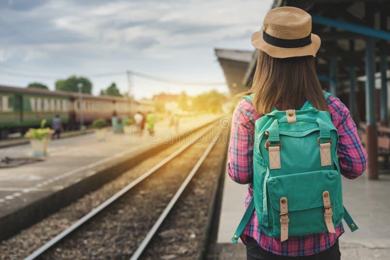 O passeio e as esperas da mulher do viajante treinam na plataforma railway, alargamento da luz de Sun imagem de stock