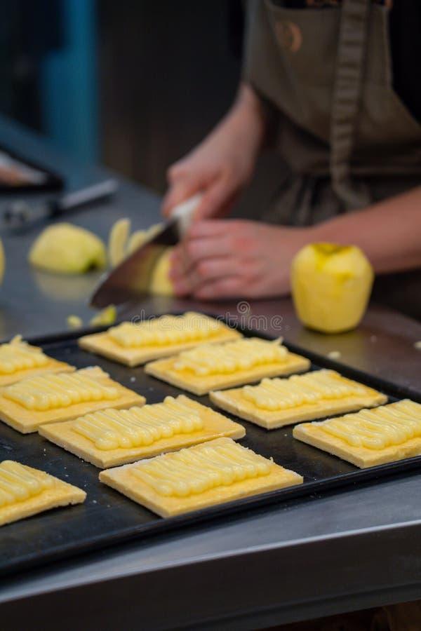 O pasteleiro do artesão prepara a torta de maçã caseiro em uns confeitos imagem de stock