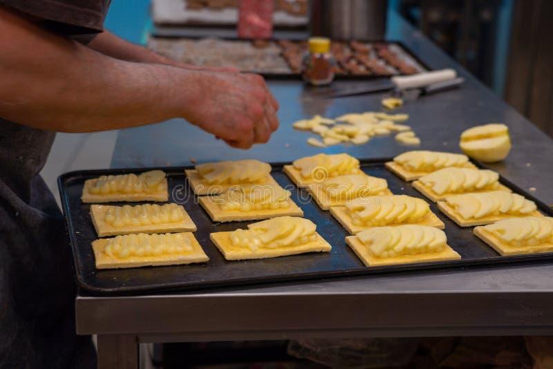 O pasteleiro do artesão prepara a torta de maçã caseiro em uns confeitos imagens de stock royalty free