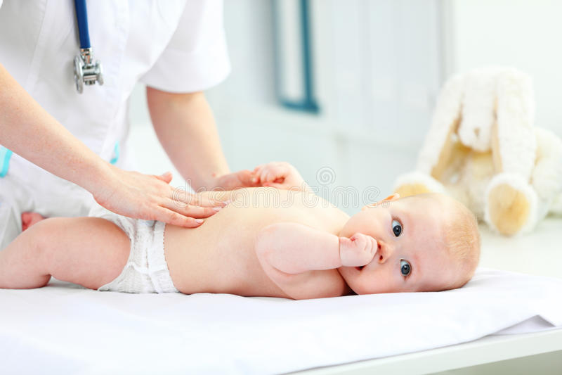 O pediatra do doutor examina a barriga do bebê foto de stock