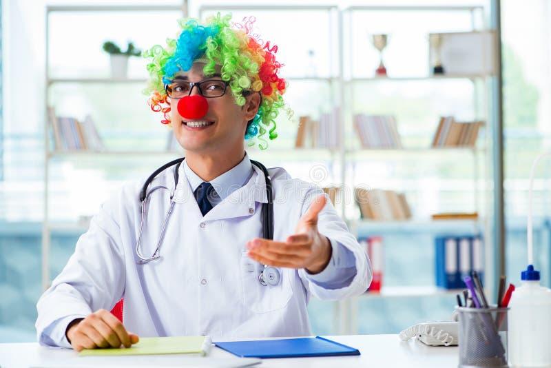 O pediatra engraçado com a peruca do palhaço na clínica do hospital fotografia de stock