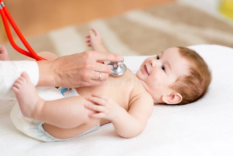 O pediatra examina três meses de bebê foto de stock