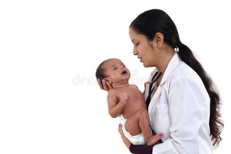 O pediatra fêmea guarda o bebê recém-nascido fotografia de stock