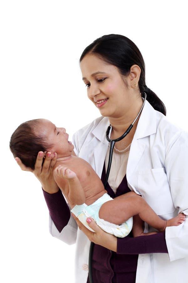 O pediatra fêmea guarda o bebê recém-nascido foto de stock royalty free