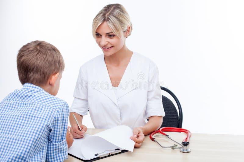 O pediatra fêmea novo bonito está vendo-a imagem de stock