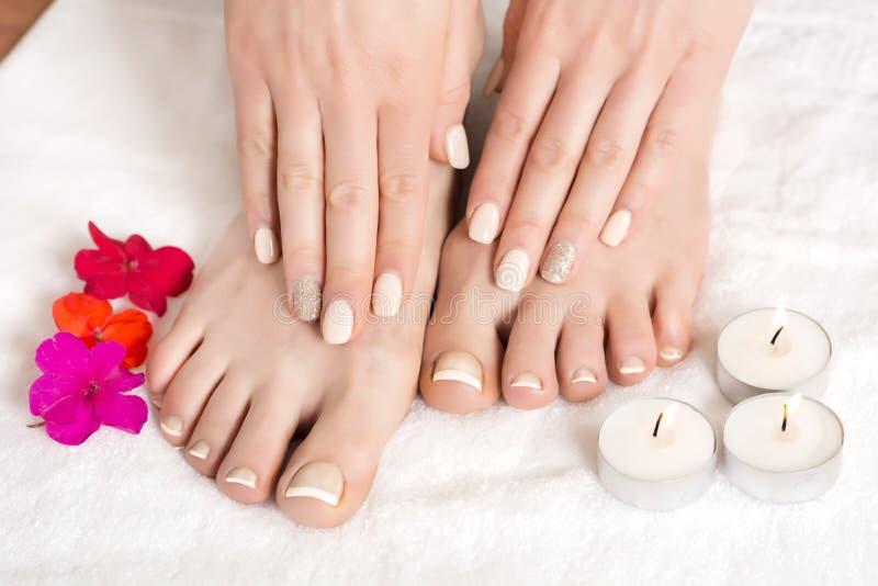 O pedicure e o tratamento de mãos de relaxamento com um vermelho florescem e velas foto de stock royalty free