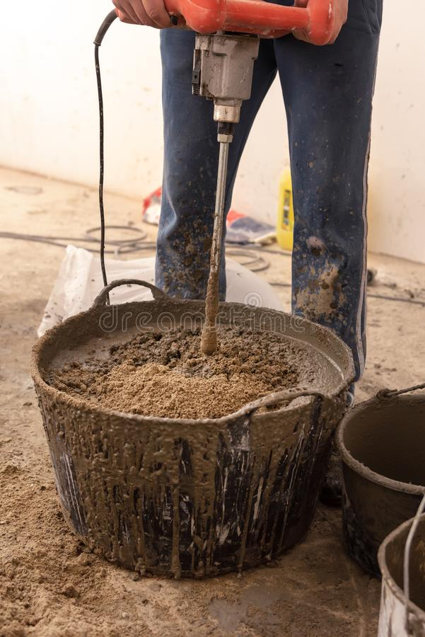 O pedreiro amassa o almofariz do cimento para derramar o dircurso concreto fotografia de stock