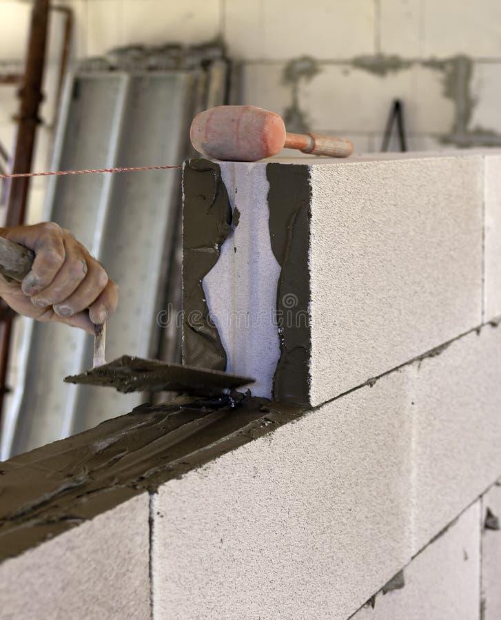 O pedreiro executa uma alvenaria interna obstrui o concreto ventilado foto de stock royalty free
