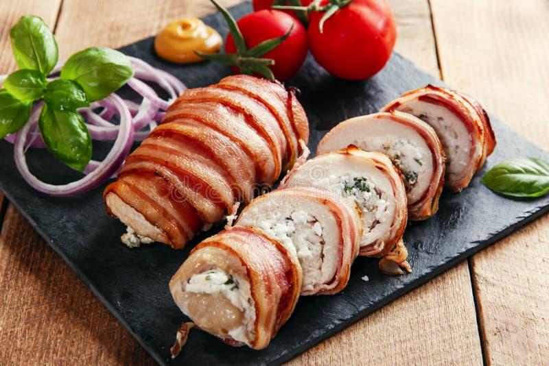 O peito de frango encheu o queijo e as ervas de feta no bacon imagens de stock royalty free