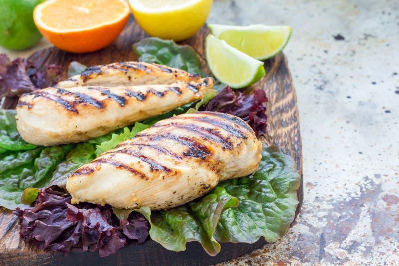 O peito de frango grelhado na marinada do citrino nas folhas da salada e na placa de madeira, horizontais, copia o espaço fotografia de stock royalty free