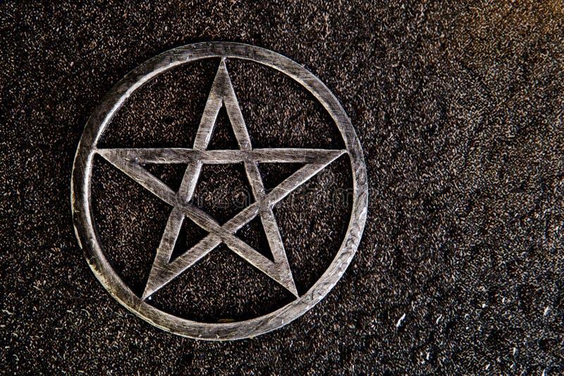 O pentagram cinzento do metal no fundo da ardósia com água deixa cair foto de stock
